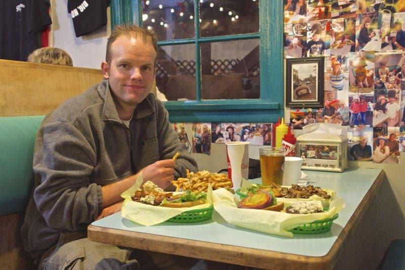 man eating garlic fries Sylvester's Burgers Los Osos