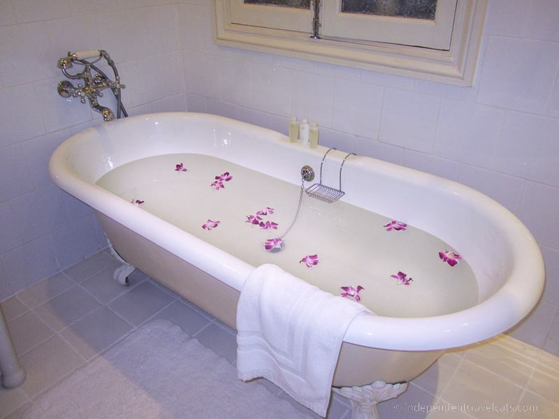 bathtub with flower petals taking a bath while traveling travel tips for bath lovers